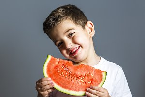 Funny kid eating watermelon indoor