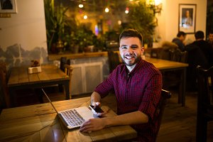 A young handsome Caucasian man with beard and toothy smile in red checkered shirt is working behind laptop sitting at wooden table. Uses holds mobile phone in hand. In the evening at the coffee shop
