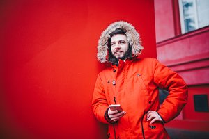 handsome young male student with toothy smile and beard stands on red wall background in bright red winter jacket with hood with fur, Uses, holds mobile phone with hand in pocket. Winter cold weather