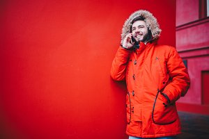 handsome young male student with a toothy smile and a beard stands on a red wall background in a bright red winter jacket with a hood with fur in winter. Uses a mobile phone, talk and call