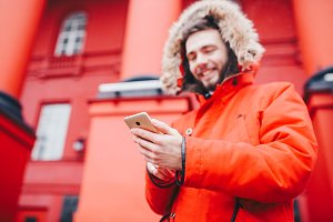 handsome young male student with toothy smile and beard stands on red wall background, facade of educational institution in red winter jacket with hood with fur, Uses finger on screen of mobile phone