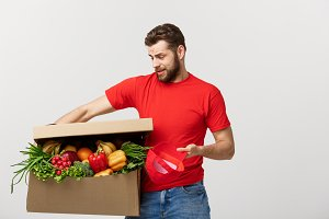 Delivery Concept: Handsome delivery man is holding a heavy grocery box isolated over grey background.