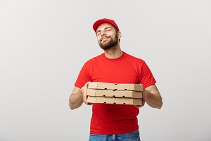 Delivery Concept: Handsome Pizza delivery man showing delicious expression over grey background