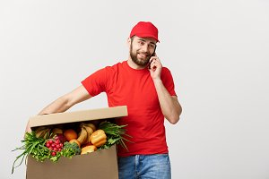 Delivery man holding paper box with food and making a call with mobile phone isolated over grey background.