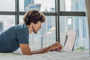 Young man is working on a laptop in his bed on a background of a panoramic window overlooking the skyscrapers. Freelancer, remote work, work from home