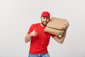 Pizza delivery concept. Young handsome delivery man showing pizza box and holding thumb up sign. Isolated on white background