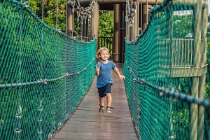 The boy is running on a suspension bridge in Kuala Lumpur, Malaysia