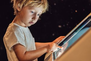 The boy uses the touch screen in the dark