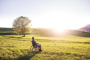 A woman in wheelchair in nature at sunset.
