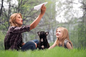 Children play with a paper airplane. Nature, grass. Cute dog with children