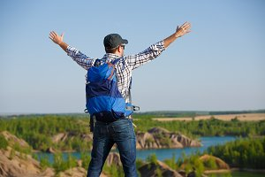 Image back of tourist man with backpack ,hands up on hill in background of mountain expanses, blue sky