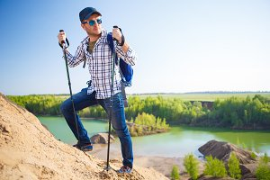 Image of tourist man with backpack with sticks for walking on hill