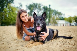 Portrait of a girl with a dog by a German shepherd.
