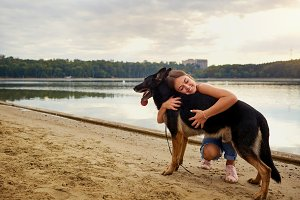 A girl hugs her dog on the beach in a park.