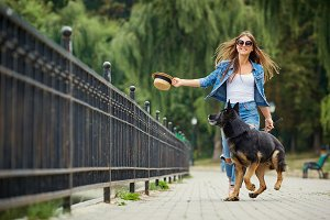 A young girl is walking with a dog in the park.