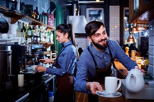 Bartender waiter with a kettle and mug of coffee tea working in