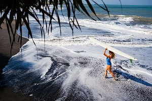 Surfer girl on black sand beach