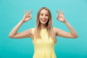 Happy young woman showing ok sign with fingers with big smile isolated on a blue background