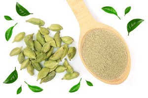 Green cardamom seeds and powder in a wooden spoon isolated on white background decorated with leaves. Top view. lay flat