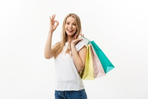 Smiling attractive woman holding shopping bags doing ok sign on white background with copyspace