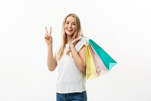 Smiling attractive woman holding shopping bags doing peace sign on white background with copyspace