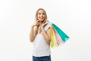 Shopping attractive woman pointing at blank Space. Shopping bags.
