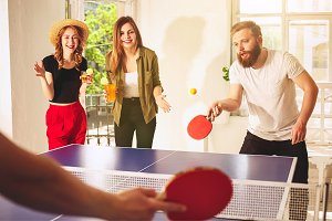 Group of happy young friends playing ping pong table tennis