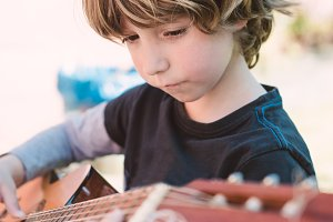 boy playing spanish guitar