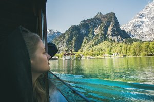 Young woman traveler looking out of window on boat trip at Konigsee Lake in berchtesgaden in Bavaria, Germany