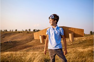 Boy child pilot with wings on nature