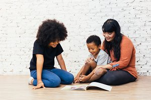 Mother reading a fairy tale fable story for kids at home. African American happy family concept