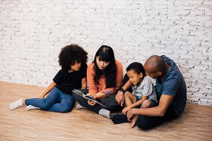 African American parents reading a fairy tale fable story for kids at home. Happy family sitting on the floor indoors