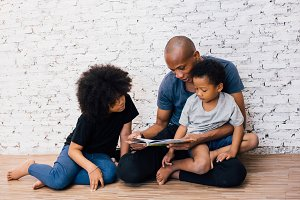 African American father reading a fairy tale fable story for kids at home. Happy family sitting on the floor indoors