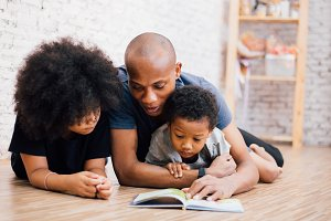 African American father reading a fairy tale fable story for kids at home. Happy family lying on the floor indoors