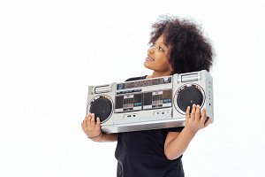 Cute and smiling African American kid holding a musical jukebox isolated over white background