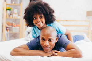 African American family of two, child sitting on father's back at home