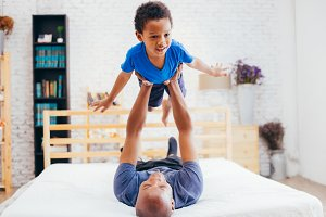 African American family of two, father lifting son up high on bed at home