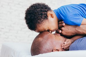 African American family of two, son looking at father on bed at home