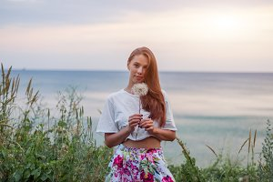 Happy beautiful woman blowing dandelion over sky and sea background, having fun and playing outdoor, teen girl enjoying nature, summer vacation and holidays, young pretty female holding flower