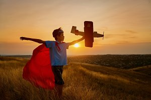 A happy boy in a superhero costume is playing with an airplane.
