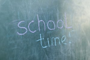 Chalkboard with wooden frame and the text school time