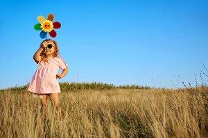 Little girl in pink dress in summer field.