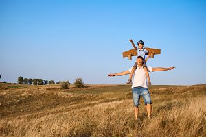 Son on the shoulders of his father in the open air in the field