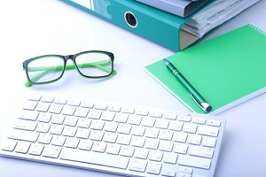 Work place table with folders file on it and modern laptop, pen, glasses and textbook lying near on a white background.