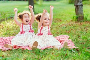 Happy twin sisters children. Girls sister in a park at a picnic