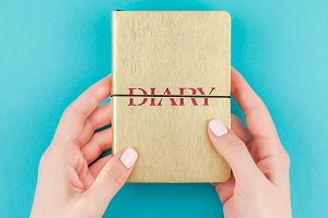 Woman hands holding golden diary