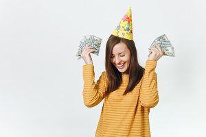 Beautiful caucasian lucky young happy woman in yellow clothes, birthday party hat holding wad of cash money, celebrating holiday on white background isolated for advertisement. Winner with dollars.