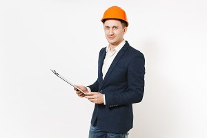 Young handsome successful businessman in dark suit, protective construction helmet holding clipboard with papers document isolated on white background. Male worker for advertisement. Business concept.