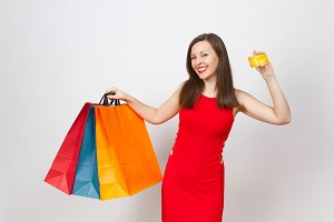 Attractive glamour fashionable young brown-hair woman in red dress holding credit card, multi colored packets with purchases after shopping isolated on white background. Copy space for advertisement.