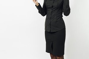 Full length portrait of angry caucasian young brown-hair business woman in black classic shirt and skirt talking, screaming on mobile phone isolated on white background. Copy space for advertisement.